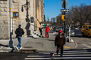 A man with a red baseball cap walks across the crosswalk with his small dog outside Holy Trinity Lutheran Church, West 65th Street, yellow taxi and cars are passing traffic along Central Park West, New York City, New York, United States of America.