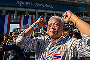 "15 JANUARY 2014 - BANGKOK, THAILAND:  SUTHEP THAUGSUBAN, former Deputy Prime Minister of Thailand and leader of the Shutdown Bangkok anti-government protests, walks through the protest site in the Asoke intersection. Tens of thousands of Thai anti-government protestors continued to block the streets of Bangkok Wednesday to shut down the Thai capitol. The protest, ""Shutdown Bangkok,"" is expected to last at least a week. Shutdown Bangkok is organized by People's Democratic Reform Committee (PRDC). It's a continuation of protests that started in early November. There have been shootings almost every night at different protests sites around Bangkok. The malls in Bangkok are still open but many other businesses are closed and mass transit is swamped with both protestors and people who had to use mass transit because the roads were blocked.   PHOTO BY JACK KURTZ"