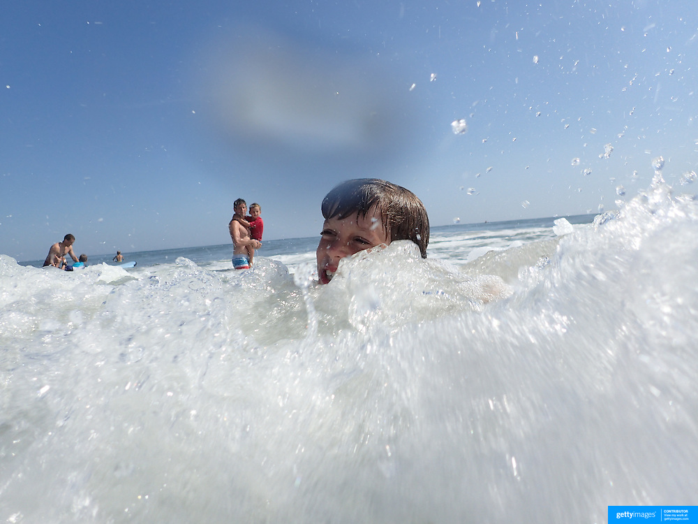 A young boy in the surf in the height of summer on Cisco Beach, Nantucket, Nantucket Island, Massachusetts, USA. Photo Tim Clayton