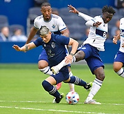 May 16, 2021 - Kansas City, KS, United States:  Sporting Kansas City forward Alan Pulido (9) falls to the turf between Vancouver Whitecaps defender Derek Cornelius (13, behind Pulido) and Vancouver Whitecaps midfielder Janio Bikel (19, right) as he moves towards the Vancouver goal.   Sporting KC beat the Vancouver Whitecaps FC 3-0 in a Major League Soccer game. <br /> Photo by Tim Vizer/Polaris