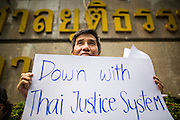 25 JANUARY 2013 - BANGKOK, THAILAND:  A freedom of speech activist pickets the Criminal Court building in Bangkok. About 70 people protested on behalf of freedom of speech and expression at the Criminal Court building in Bangkok Friday. The protest was called as a result of the 10 year sentence handed down against magazine editor Somyot Prueksakasemsuk on Lese Majeste charges earlier in the week. The protesters burned several legal documents to demonstrate they said was their loss of free speech during the protest.    PHOTO BY JACK KURTZ