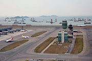 Aeroplanes on one of the two runways at Hong Kong International Airport in Chek Lap Kok, Hong Kong. Numerous cargo carriers can be seen in the South China sea as well as several islands.