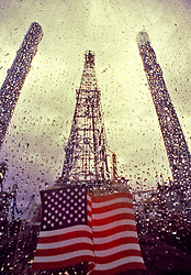 View of an oil drilling rig derrick from the tool pusher's window featuring an American flag sticker.