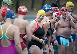 © Licensed to London News Pictures. 25/12/2017. London, UK. A competitor wearing Santa hat as members of the Serpentine Swimming Club prepare to brave the cold waters at the Serpentine Lake in Hyde Park, London to compete for the traditional Peter Pan Cup on Christmas Day, December 25, 2017. Photo credit: Ben Cawthra/LNP