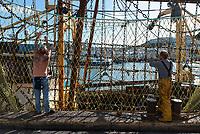 "2 fishermen from the ""Pamela Jill"" repair the fishing nets in Brixham, Devon, Great Britain. Le ramendage des filets de pêches à bord du Pamela Jill, Port de Brixham, Devon, Grande-Bretagne."
