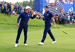 Team Europe's Thorbjorn Olesen and Team Europe's Rory McIlroy celebrate going 1up on the 8th during the Fourballs match on day one of the Ryder Cup at Le Golf National, Saint-Quentin-en-Yvelines, Paris.