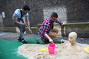 Summertime in London, England, UK. For the first time the Royal Academy and its artists take to the streets of Mayfair with Burlington Gardens pedestrianised and the street transformed for a day with this fun arts event. Green keepers tend to the bunker sand trap on the crazy golf course
