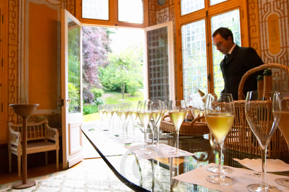 In the tasting room a waiter pouring champagne for a tasting. Champagne glasses on a row with a view out to the garden behind the building at Champagne Deutz in Ay, Vallee de la Marne, Champagne, Marne, Ardennes, France, low light grainy grain