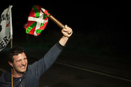 """A man carries the baton as he runs on the 20th Korrika. Tutera (Basque Country). April 1, 2017. The """"Korrika"""" is a relay course, with a wooden baton that passes from hand to hand without interruption, organised every two years in a bid to promote the basque language. The Korrika runs over 11 days and 10 nights, crossing many Basque villages and cities. This year was the 20th edition and run more than 2500 Kilometres. Some people consider it an honour to carry the baton with the symbol of the Basques, """"buying"""" kilometres to support Basque language teaching. (Gari Garaialde / Bostok Photo)"""