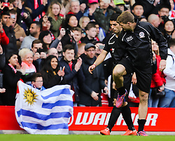Luis Suarez walks with Steven Gerrard past a fan holding up a Uruguayan flag - Photo mandatory by-line: Dougie Allward/JMP - Mobile: 07966 386802 - 29/03/2015 - SPORT - Football - Liverpool - Anfield Stadium - Gerrard's Squad v Carragher's Squad - Liverpool FC All stars Game