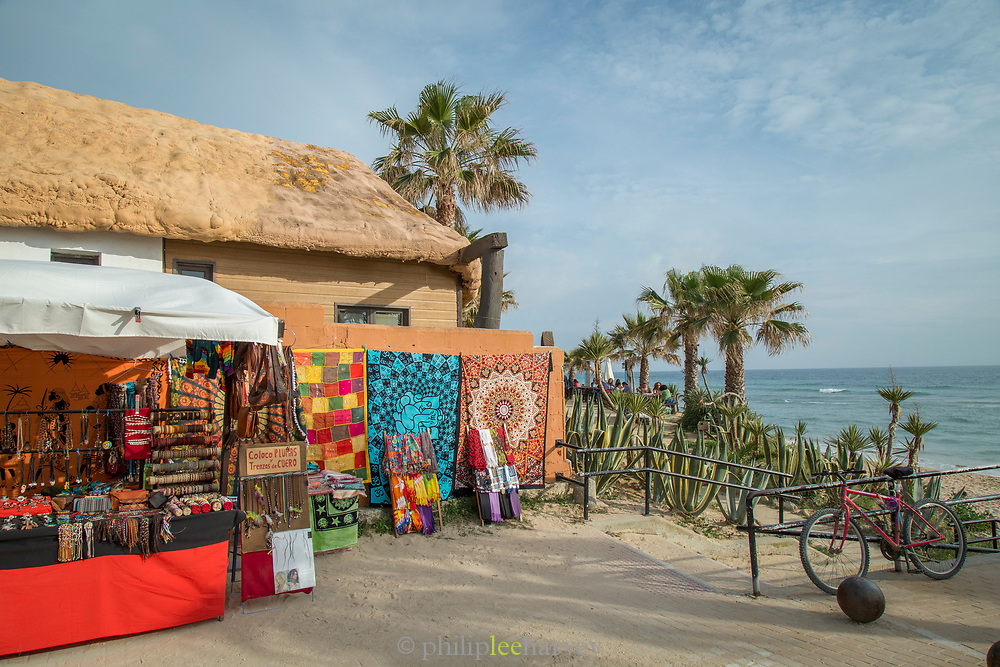Market stall by beach with sea in background, Cadiz, Andalusia, Spain