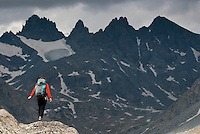 A young woman takes in the view while hiking in Titcomb Basin, Wind River Mountains, Wyoming.