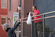 An employee of a food seller delivers to a customer at the back entrance of the Easton Public Market on Mar. 21, 2020, as the space in Easton, Pennsylvania is closed to customers. Businesses inside still offer delivery outside after customers order and pay through phone orders or on an app. Communities across the Lehigh Valley are adjusting to life during the coronavirus pandemic that is impacting the daily lives of Pennsylvania residents both socially and economically. (Photo by Matt Smith)