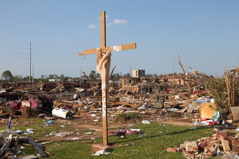 A cross stands in the middle of rubble left in a tornado's wake. Parts of Tuscaloosa , in west central Alabama  remain in a state of ruin  two weeks after it was hit by an F-4 ( possibly an F-5) tornado, one of an estimated 300 that struck Alabama and the neighboring states on April 27th , 2011.