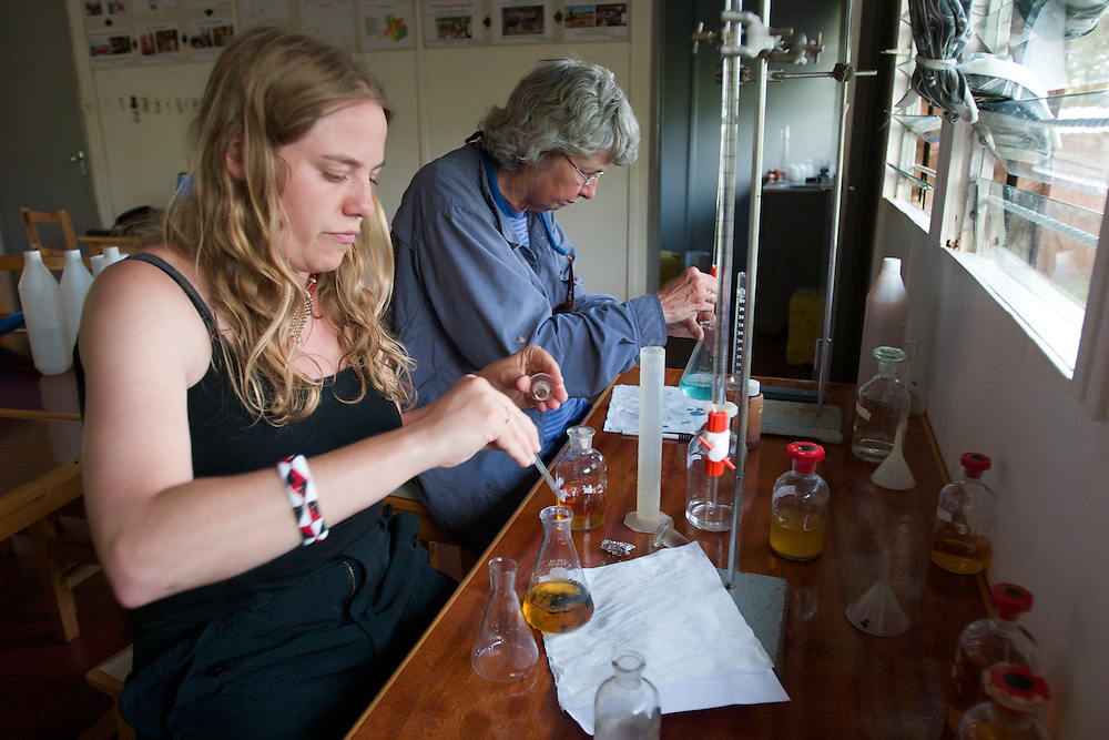 In the lab at the Earthwatch base in Wamba, two volunteers pipette chemical solutions to measure the amount of mineral in the water samples collected.