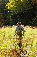 Jay Ericson walking along the bank while fly fishing for trout on the upper Connecticut River in northern New Hampshire.