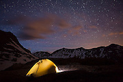 The Milky Way sparkles in the night sky over an illuminated tent and the Never Summer Mountains of Colorado (Baker Mountain, Mount Stratus and Mount Numbus).