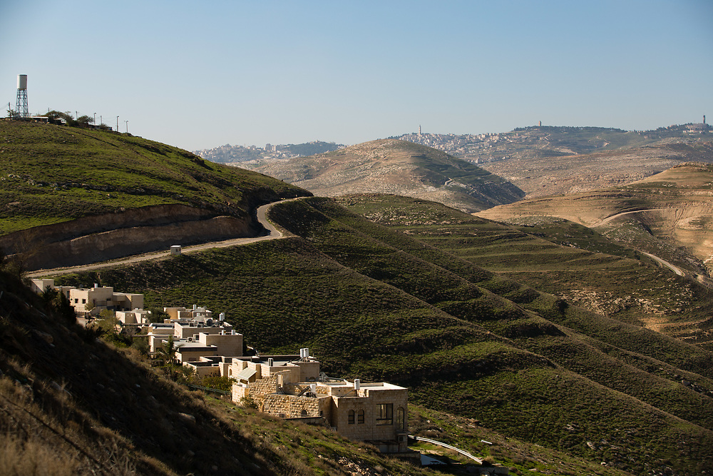 A general view of houses in Nofei Prat settlement (foreground) and Jerusalem (background) from a terrace overlooking Wadi Qelt (Nahal Prat in Hebrew) at  'Nof Canaan' bed and breakfast, which is advertised on Airbnb international home-sharing site and rental listings service, in the West Bank Jewish settlement of Nofei Prat, on January 28, 2016.