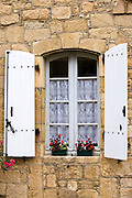 Traditional French window lace curtains shutters window boxes in picturesque Sarlat, Dordogne, France
