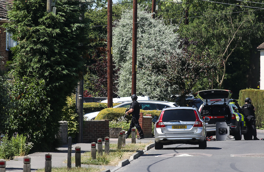 """Armed police surround a house in Kidlington, Oxfordshire on July, 9, 2013.<br /> <br /> An armed man is holed up in a property where he was holding his two-year-old twin daughters, police have said.<br /> <br /> Thames Valley Police said they are in """"regular communication"""" with the 38-year-old, who released both girls from the flat hours after a woman escaped and raised the alarm.<br /> <br /> Photo By Ki Price"""