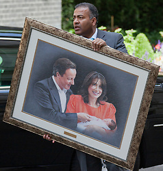© Licensed to London News Pictures. LONDON, UK  01/07/11. An aid to the President of Pakistan, Asif Ali Zardari, carries a portrait of British Prime Minister David Cameron, his wife Samantha and their daughter Florence, as the president arrives at 10 Downing Street for talks. Discussions between Mr Cameron and Mr Zadari are expected to discuss allied troop withdrawals from Afghanistan and security on the Afghanistan/Pakistan border.  Please see special instructions for usage rates. Photo credit should read Matt Cetti-Roberts/LNP