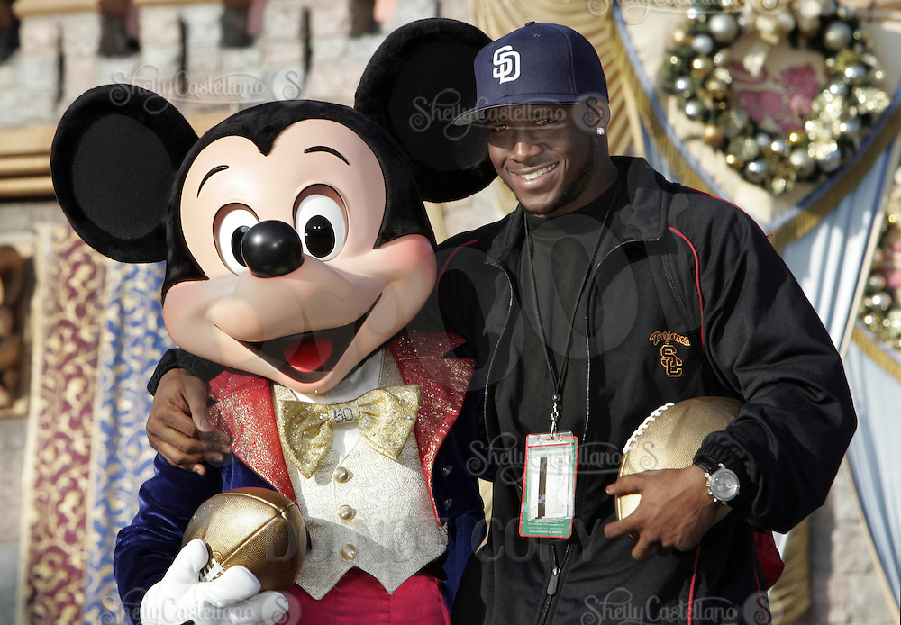 29 December 2005: University of Southern California USC Trojans college football player poses with Mickey Mouse and a gold football during a visit to Disneyland on Thursday. Both teams will play for the National Championship in the Rose Bowl on January 4, 2006.