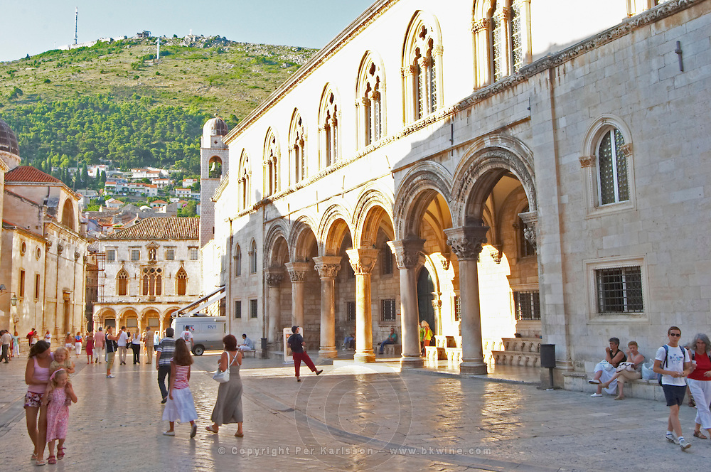 Tourists walking past in front of arched porch of the Rector's Palace Knezev Dvor on the Pred Dvorom street and in the background the arched porch and facade of the Sponza palace Dubrovnik, old city. Dalmatian Coast, Croatia, Europe.