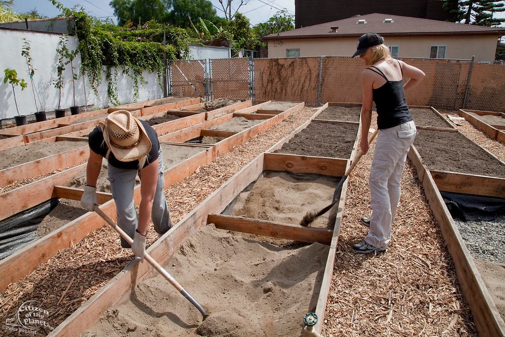 August 14, 2010. Isabel and Aeryn fill their planting box with the newly arrived soil. The Venice Garden broke ground in April, 2010. Soil tests revealed high levels of arsenic and lead because of previous uses which included a railroad line going through the lot. Steps were taken which included adding protective layers and adding new soil. Planting began in August and the first harvest was in October, 2010. Venice, California, USA