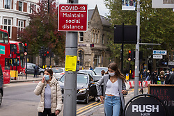 © Licensed to London News Pictures. 17/10/2020. LONDON, UK. Women wearing facemasks pass a social distancing sign in Ealing, west London.  The Office for National Statistics (ONS) has reported that the confirmed coronavirus cases in the capital exceed 67,000, with Ealing having the highest Covid-19 rate amongst London Boroughs at 144 cases per 100.  Following the UK Government's announcement, the capital has today moved from Tier 1 to Tier 2, meaning a ban on indoor social mixing between households in the capital.  Photo credit: Stephen Chung/LNP