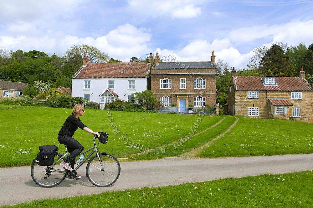 A tourist is cycling in Kilburn, Yorkshire, England, United Kingdom.