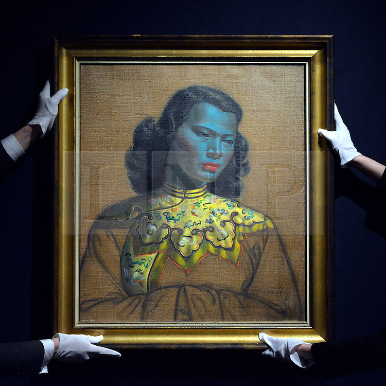 """© Licensed to London News Pictures. 18/03/2013. London, UK A gallery assistant hangs the painting. Press call before the auction of """"Chinese Girl"""" by Vladimir Tretchikoff at Bonhams in London today 18th March 2013. The painting is said to be the most widely reproduced and recognisable painting in the world because of its wide reproduction in 1950's art prints. It is expected to fetch 300,000-500,000 GBP at auction on the 20th March. Photo credit : Stephen Simpson/LNP"""
