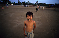 Young kid in district 2 plays football with his friends on an area of land that has been cleared for development of a highway that will connect district 2 to district 1 of Ho Chi Minh City. 2007.