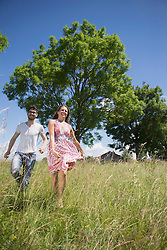 Mid adult couple running through grass on meadow in the countryside, Bavaria, Germany