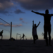 Locals celebrate during a game of foot volley, a hybrid game combining beach volley ball and football at Copacabana beach, Rio de Janeiro,  Brazil. 5th July 2010. Photo Tim Clayton..The beaches of Rio de Janeiro, provide the ultimate playground for locals and tourists alike. Beach activity is in abundance as beach volley ball, football and a hybrid of the two, foot volley, are played day and night along the length and breadth of Rio's beaches. .Volleyball nets and football posts stretch along the cities coastline and are a hive of activity particularly at it's most famous beaches Copacabana and Ipanema. .The warm waters of the Atlantic Ocean provide the ideal conditions for a variety of water sports. Walkways along the edge of the beaches along with exercise stations and cycleways encourage sporting activity, even an outdoor gym is available at the Parque Do Arpoador overlooking the ocean. .On Sunday's the main roads along the beaches of Copacabana, Leblon and Ipanema are closed to traffic bringing out thousands of people of all ages to walk, run, jog, ride, skateboard and cycle more than 10 km of beachside roadway. .This sports mad city is about to become a worldwide sporting focus as they play host to the world's biggest sporting events with Brazil hosting the next Fifa World Cup in 2014 and Rio de Janeiro hosting the Olympic Games in 2016...
