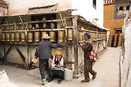 Tibetan men spin prayer wheels around a small temple oon the Barkor in Lhasa, Tibet.