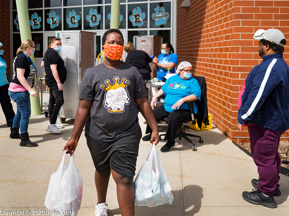 22 APRIL 2020 - DES MOINES, IOWA: A student walks home after getting grab and go meals at Edmunds Elementary School. Schools in Iowa are closed for the rest of the school year because of the COVID-19 (Coronavirus/SAR-CoV-2) pandemic. Des Moines Public Schools expanded their school lunch and distance learning efforts this week. Lunches are being distributed at all of the district's elementary and middle schools and officials have started distributing computers so students can participate in distance learning. The meal distribution was done according to social distancing guidelines.           PHOTO BY JACK KURTZ