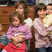 """CAPTION: Oksana, surrounded by her precious children. """"Without Partnership For Every Child's short break service"""", she says, """"my children would have gone into a children's home and I would never have got them out"""". NAME MUST BE CHANGED. LOCATION: St Petersburg, Russia. INDIVIDUAL(S) PHOTOGRAPHED: Alexander Orlov (son), Oksana Orlova (mother), Kseniya Orlova (baby), Diana Orlova (girl behind) and Elena Orlova (girl in front)."""