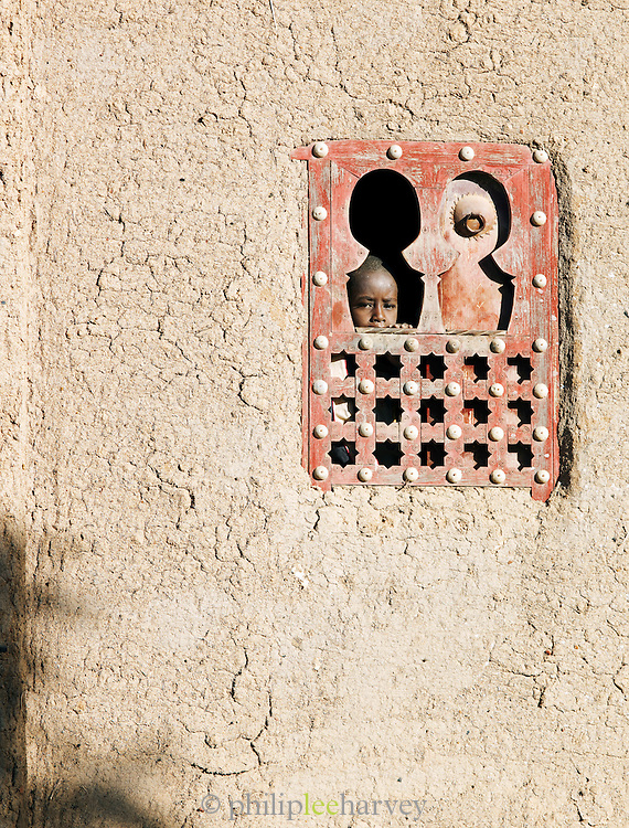 A child looks out from a window of a mud built house in Djenné, Mali