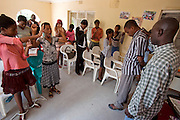 Worshipers at  a Sunday morning church service at the home of Pastor John (far left with shaved head and checkered shirt). Pastor John runs Windows of Hope, a christian church mission in Ghanzi, Botswana that helps orphans and other children in need. Some of the children under his care have been orphaned by AIDS.