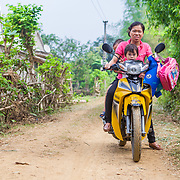 CAPTION: Hue takes her children to school on the family's recently purchased motorbike, saving her time every day. LOCATION: Coong Village, Huy Tuong, Son La Province, Vietnam. INDIVIDUAL(S) PHOTOGRAPHED: Lo Thi Hue (above) and Ha Thi Huong (below).