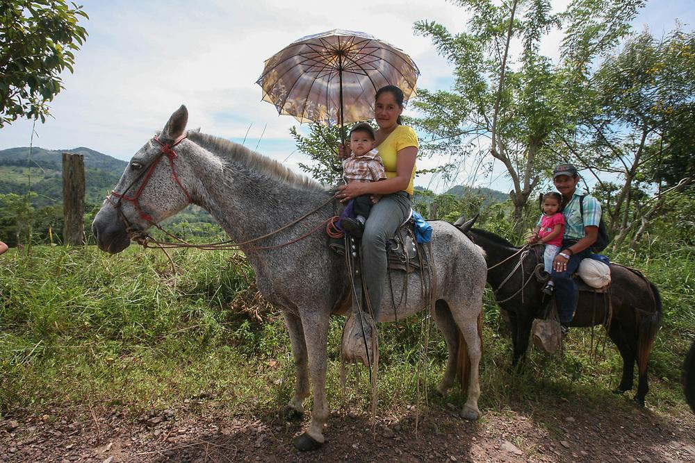 A Waslala family travelling on horseback with a parasol. Cooperativa de Servicios Agroforestal y Comercialización de Cacao, CACAONICA, is located in Waslala, Nicaragua and is Fairtrade-certified.