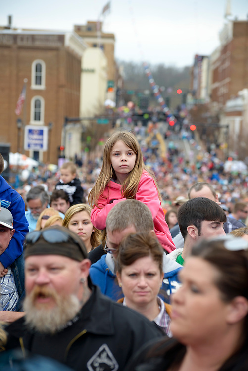 Greeneville, Tennessee - March 30, 2013: A young girl sits on an adult's shoulders, part of a large crowd on Main Street in Greeneville, Tennessee. The crowd had gathered to watch a free concert by The Band Perry, whose roots are in Greeneville.