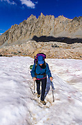Backpacker crossing snowfield on the Bishop Pass Trail, John Muir Wilderness, Sierra Nevada Mountains, California USA