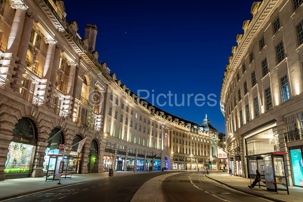 A man waits for a bus on an eerily quiet Regent Street in what would normally be the evening rush hour in London on March 27th, 2020. The centre of London is extremely quiet with almost every business closed and very few people about because of the Governments lockdown measures due to the Coronavirus crisis.