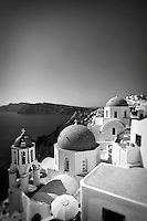 Black and white photo of buildings on a cliff with blue domed rooftops in Santorini, Greece, with a view of the Aegean sea in the background.