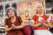 13 APRIL 2013 - BANGKOK, THAILAND:  Women pray in front of a portrait of Bhumibol Adulyadej, the King of Thailand, at the Bangkok City Hall building on Songkran. Songkran is the traditional Thai New Year's Festival. It is held April 13-16. Many Thais mark the holiday by going to temples and making merit by giving extra alms to monks or offering extra prayers. They also mark Songkran with joyous water fights. Songkran has been a national holiday since 1940, when Thailand moved the first day of the year to January 1.   PHOTO BY JACK KURTZ