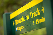 Close-up of a trail post with yellow letters on a green background near the beginning of the Routeburn Track from the Routeburn Shelter, South Island, New Zealand
