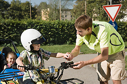 Tutor explaining quadbike to boy on driver training area