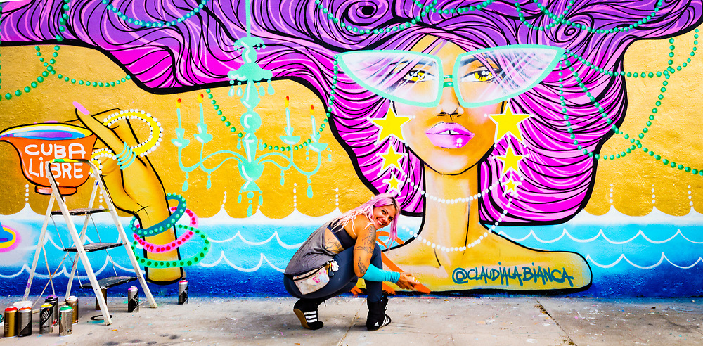 Street artist Claudia LaBianca spray-painting a mural at a vintage thrift shop in Miami's Wynwood district.