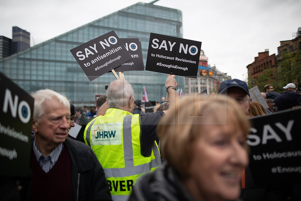 """© Licensed to London News Pictures . 16/09/2018. Manchester, UK. A man passes out placards that read """" Say no to antisemitism """" . Thousands of people including the UK's Chief Rabbi and several Members of Parliament attend a demonstration against rising anti-Semitism in British politics and society , at Cathedral Gardens in Manchester City Centre . Photo credit : Joel Goodman/LNP"""